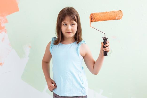 Kid in piedi con il rullo di vernice in mano.