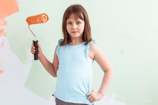 Kid in piedi con il rullo di vernice in mano