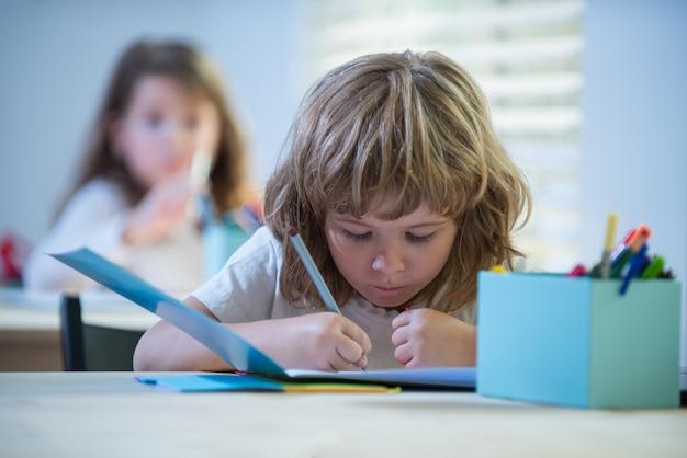 Bambino che studia a scuola scolaro che fa i compiti all'istruzione in classe per bambini