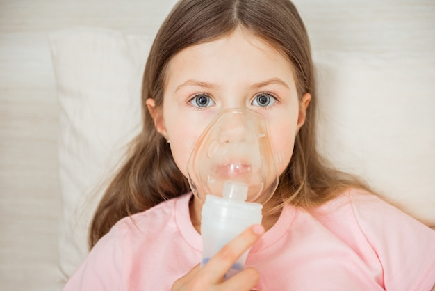 Bambino con fibrosi cistica sdraiato su un letto con maschera nebulizzatrice