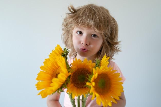 Capretto con fiori. bel bambino romantico. fronte divertente dei bambini.