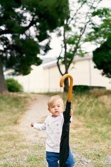 Bambino con un portaombrelli piegato sul sentiero in un parco verde