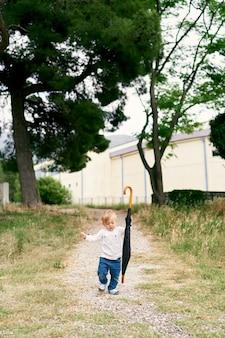 Il bambino con un ombrello piegato cammina lungo il sentiero in un parco verde
