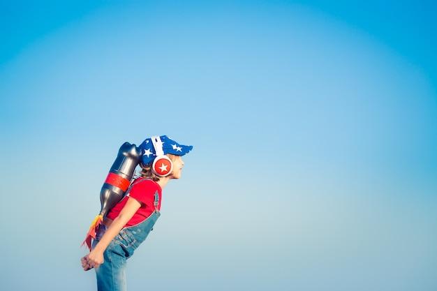 Kid con jet pack contro il cielo blu. bambino che gioca all'aperto. concetto di successo, leader e vincitore