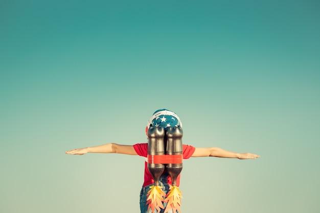 Bambino con jet pack sullo sfondo del cielo bambino che gioca all'aperto
