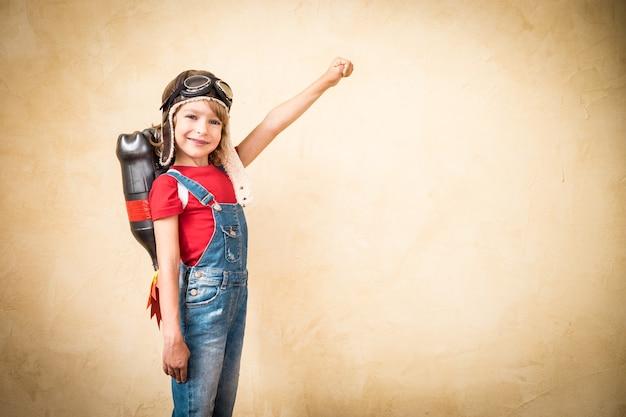 Ragazzo con jet pack. bambino che gioca in casa. concetto di successo, leader e vincitore