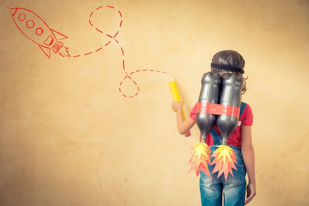 Ragazzo con jet pack disegnare schizzo sul muro. bambino che gioca in casa. concetto di successo, leader e vincitore
