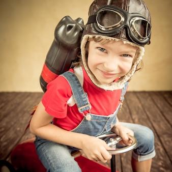 Ragazzo con jet pack alla guida di una macchinina retrò. bambino che gioca in casa. concetto di successo, leader e vincitore