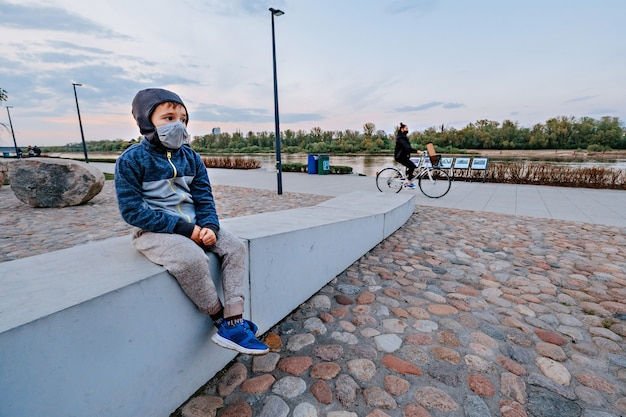 Bambino con protezione viso seduto e donna con maschera in gite in bicicletta