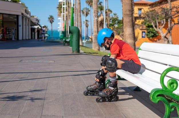 Bambino con maschera protettiva che indossa i pattini a rotelle all'aperto