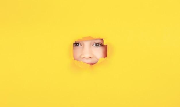 Il bambino con un sorriso a trentadue denti mostra la faccia nel foro della carta. bambino positivo con un piacevole sorriso a trentadue denti sul viso, passa attraverso un buco strappato nella carta gialla. rompere lo sfondo della carta. concetto di emozioni.
