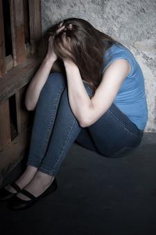 Donna rapita. vista dall'alto di una giovane donna che piange e si tiene per mano nei capelli mentre è seduta sul pavimento