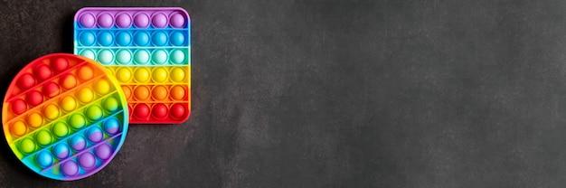 Bambini anti stress sensoriali pop it o semplici giocattoli push fidget fossette su un tavolo nero o sullo sfondo del pavimento. colore arcobaleno popit colore brillante, tendenza 2021 anno. vista dall'alto, piatto. striscione