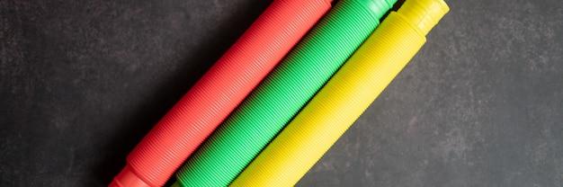 Bambini anti stress sensoriale pop tubo plastica fidget push giocattolo su un tavolo nero o sullo sfondo del pavimento. piccoli giocattoli poptube per bambini tonalità multicolore colore brillante. bandiera. vista dall'alto, disposizione piatta