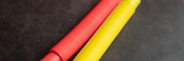 Bambini anti stress sensoriale pop tubo plastica fidget push giocattolo su un tavolo nero o sullo sfondo del pavimento. piccoli giocattoli poptube per bambini tonalità di rosso e giallo colore brillante. bandiera. vista dall'alto, disposizione piatta