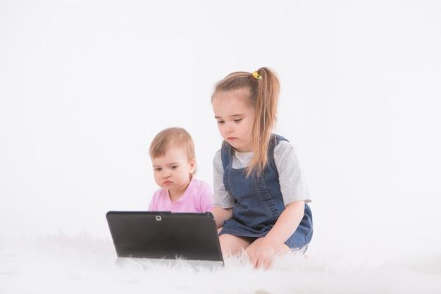 I bambini guardano i cartoni animati sul tablet. scuola a casa per le ragazze durante la quarantena