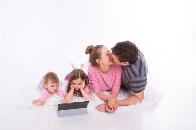 I bambini guardano i cartoni animati sul tablet. l'uomo e una donna si abbracciano. vacanze in famiglia, passatempo comune. genitori con ragazze sul pavimento