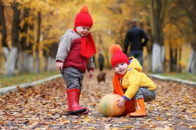 Bambini nel parco autunnale con la zucca intorno alle foglie d'autunno