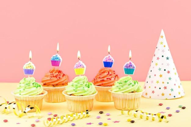 Accessori per feste di compleanno per bambini: cupcakes colorati con candele accese, cappello da festa, stelle filanti, coriandoli. copia spazio