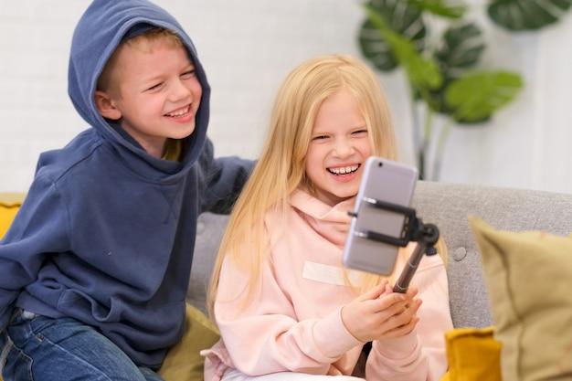 Blogger di bambini che parlano di follower, live streaming, guardando allo smartphone