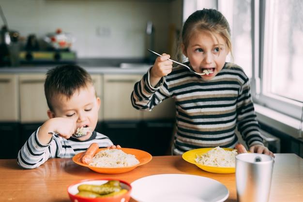 Bambini ragazzo e ragazza che mangiano pasta in cucina
