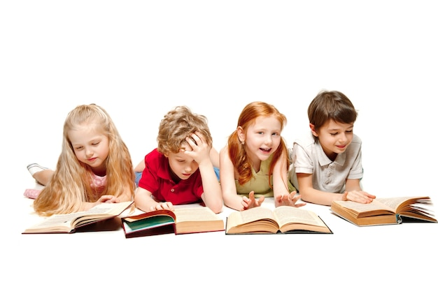 Il ragazzo e le ragazze dei bambini che posano con i libri allo studio, sorridenti, ridenti, isolati su bianco. giornata del libro, dell'educazione, della scuola, del bambino, della conoscenza, dell'infanzia, dell'amicizia, dello studio e del concetto di bambini Foto Premium
