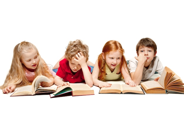 Il ragazzo e le ragazze dei bambini che posano con i libri allo studio, sorridenti, ridenti, isolati su bianco. giornata del libro, dell'educazione, della scuola, del bambino, della conoscenza, dell'infanzia, dell'amicizia, dello studio e del concetto di bambini