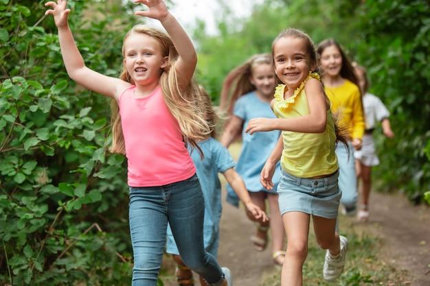 Bambini bambini che corrono sul prato verde