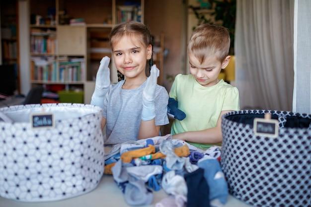 I bambini puliscono la stanza, ordinano i calzini e li sistemano in cesti personali. routine quotidiana con divertimento