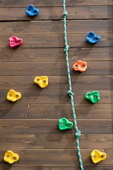 Bambini che si arrampicano sulla parete di legno all'aperto immagine verticale che si arrampica sulla parete di legno del parco giochi