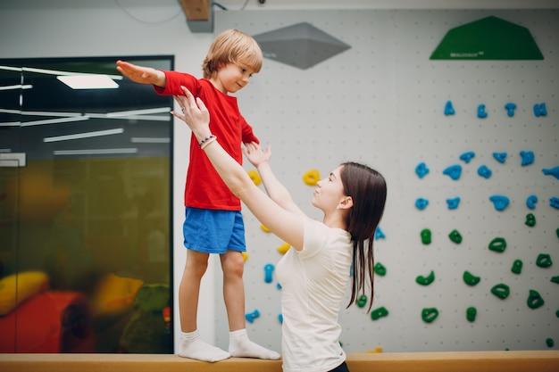 Bambini che fanno esercizi di ginnastica del fascio di equilibrio in palestra all'asilo o alla scuola elementare. concetto di sport e fitness per bambini.