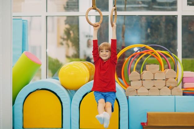 Bambini che fanno esercizi in palestra all'asilo o alla scuola elementare. concetto di anelli sportivi e fitness per bambini.