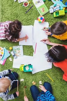 Bambini che disegnano e giocano