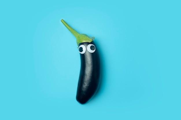Concetto di cibo per bambini. melanzane con occhi su sfondo blu colorato. verdure divertenti e cibo per bambini