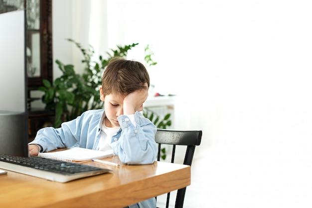 Bambini e gadget. apprendimento a distanza durante l'isolamento durante la quarantena. ragazzo e laptop a casa. stile di vita. lockdown e social distancing