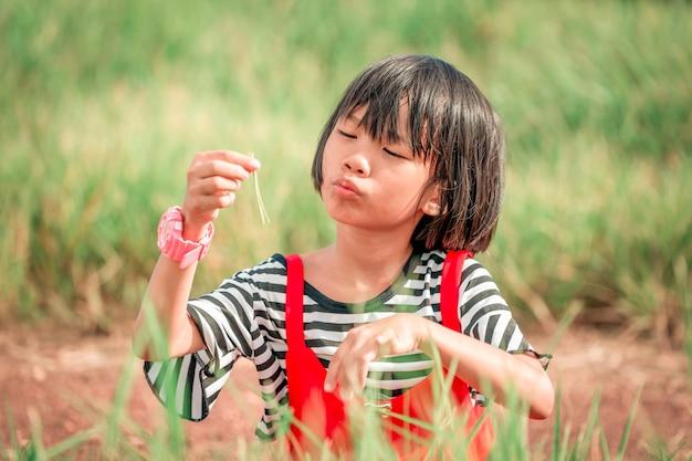 Ragazza dei bambini che gioca nei prati durante il giorno