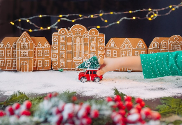 Mano dei bambini che gioca con il giocattolo dell'automobile con l'albero di natale nella città dei biscotti di pan di zenzero. messa a fuoco selettiva sul giocattolo.