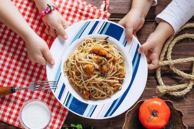 Mani dei bambini e piatto con pasta sul tavolo, cucinare a casa con vista dall'alto del bambino