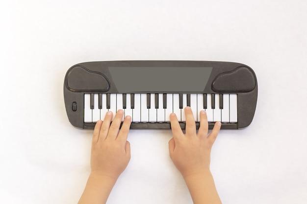 Le mani dei bambini giocano sui tasti del pianoforte, sintetizzatore giocattolo su sfondo bianco