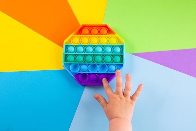 Le mani dei bambini spingono il popit sensoriale su uno sfondo colorato