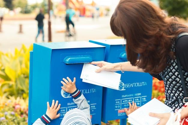 I bambini aiutano sua madre a mettere le lettere nella cassetta della posta