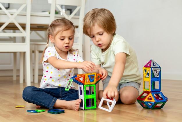 Bambini a casa che giocano insieme con i giocattoli