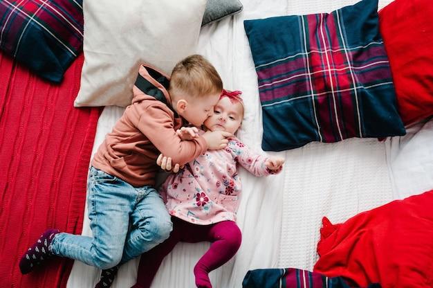 Bambini sdraiati sul letto in camera da letto vicino all'albero di natale. buon natale. vista dall'alto, flatlay. il concetto di vacanza in famiglia. avvicinamento.
