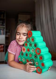 Bambini che fanno il calendario dell'avvento natalizio fatto a mano con rotoli di carta igienica a casa