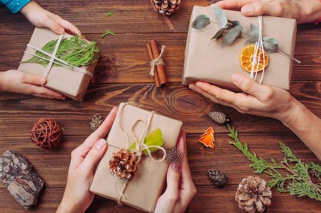 Mani di bambini, madre e nonna che tengono scatole regalo di natale decorate con dettagli naturali su superficie di legno rustica. concetto di arredamento natalizio fatto a mano ecologico. vista dall'alto, piatto.