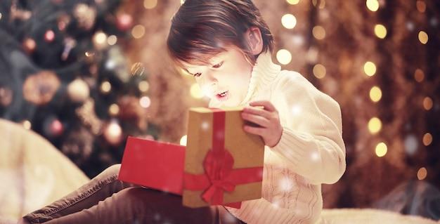 Bambini che aprono i regali di natale bambini sotto l'albero di natale con scatole regalo