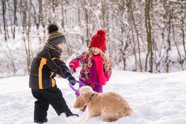 I bambini giocano con il cane nella foresta invernale