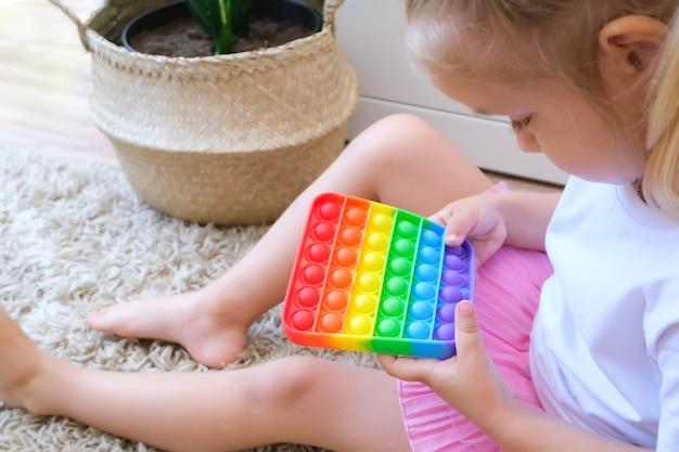 I bambini giocano con il giocattolo sensoriale pop it. sollievo dallo stress e dall'ansia. gioco di agitazione alla moda in silicone per bambini stressati