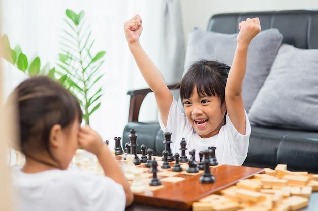 Bambini che giocano a scacchi - uno di loro ha appena catturato un pedone e festeggia