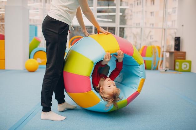 Bambini che giocano in palestra all'asilo o al concetto di sport e fitness per bambini delle scuole elementari